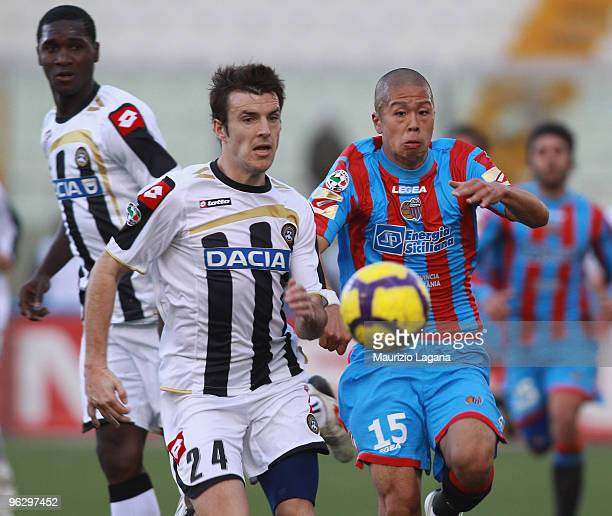 Takayuki Morimoto of Catania Calcio is challenged by Aleksandar Lukovic of Udinese Calcio during the Serie A match between Catania and Udinese at...