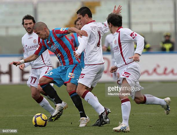 Takayuki Morimoto of Catania Calcio is challenged by Romano Perticone of AS Livorno during the Serie A match between Catania and Livorno at Stadio...