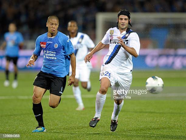 Takayuki Morimoto of Novara Calcio competes for the ball with Cristian Chivu of FC Inter Milan during the Serie A match between Novara Calcio and FC...