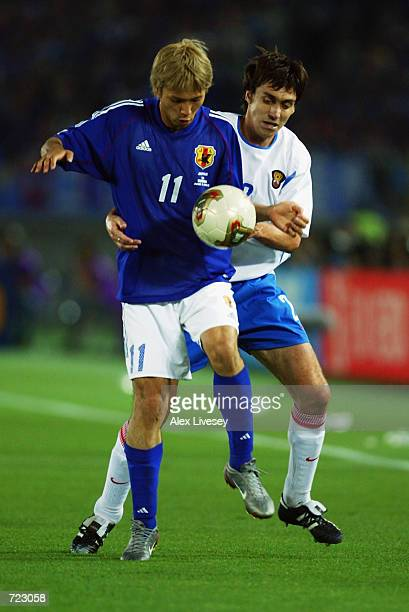 Takayuki Suzuki of Japan holds the ball up against Yuri Kovtun of Russia during the FIFA World Cup Finals 2002 Group H match played at the...