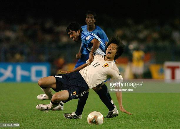 Takayuki Suzuki of Japan is tackled by Mahesh Gawli of India during the FIFA World Cup Asian Qualifier match between India and Japan at Saltlake...