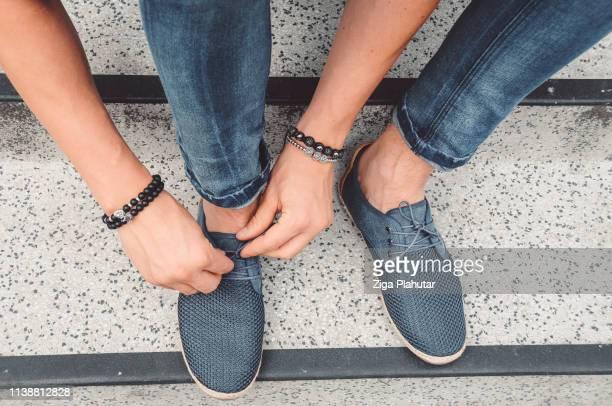 dê uma caminhada em meus sapatos-mãos amarrando cadarços - sapato - fotografias e filmes do acervo