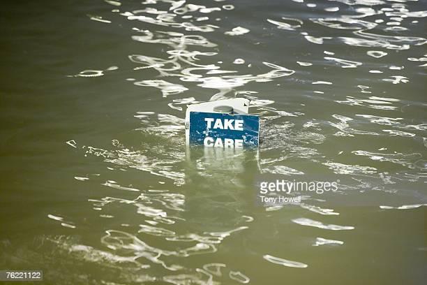 Take Care sign underwater, Weston-Super-Mare, Somerset, England