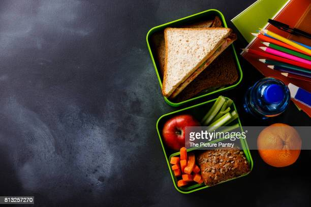 Take out food Lunch box with Sandwiches and vegetables, bottle of water and school supplies copy space