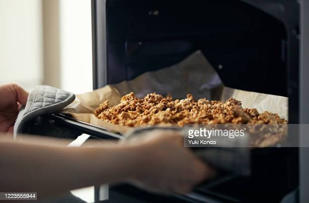 take the homemade granola out of the oven. - granola stock pictures, royalty-free photos & images