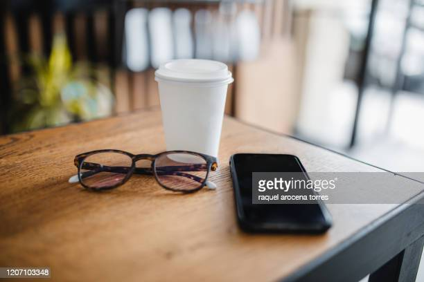 takeaway coffee on table with see glasses and mobile phone inside coffee shop - servierfertig stock-fotos und bilder