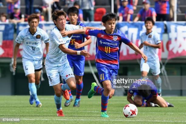 Takefusa Kubo of FC Tokyo and Taishi Nishioka of FC Ryukyu compete for the ball during the JLeague J3 match between FC Tokyo U23 and FC Ryukyu at...