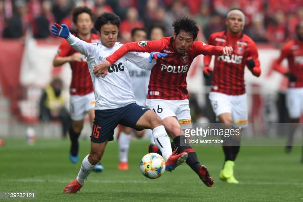 Takefusa Kubo of FC Tokyo and Takuya Aoki of Urawa Red Diamonds compete for the ball during the JLeague J1 match between Urawa Red Diamonds and FC...