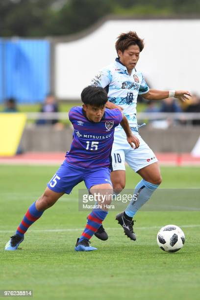 Takefusa Kubo of FC Tokyo and Yu Tomidokoro of FC Ryukyu compete for the ball during the J.League J3 match between FC Tokyo U-23 and FC Ryukyu at...