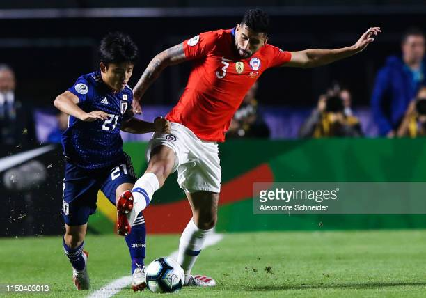 Takefusa Kubo of Japan and Gullermo Maripan of Chile compete for the ball during the match between Japan and Chile for the Copa America 2019 at...