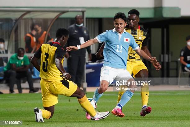 Takefusa Kubo of Japan and Uzair Alhassan of Ghana compete for the ball during the U-24 international friendly match between Japan and Ghana at the...