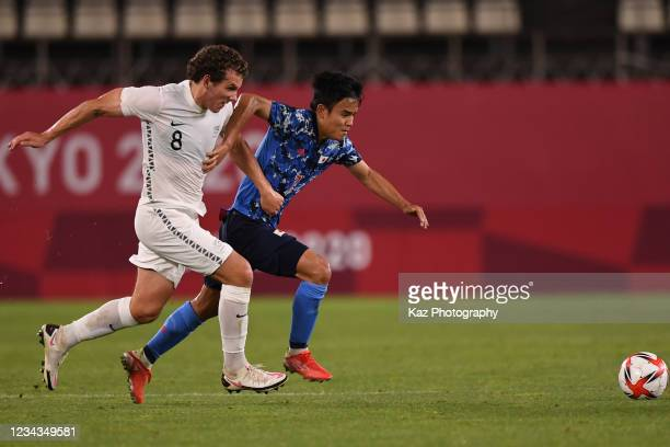 Takefusa Kubo of Japan dribbles the ball under the puressure from Joe Bell of New Zealand during the Men's Quarter Final match on day eight of the...