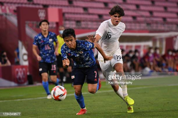 Takefusa Kubo of Japan dribbles the ball under the puressure from Matthew Garbett of New Zealand during the Men's Quarter Final match on day eight of...
