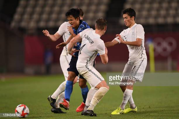 Takefusa Kubo of Japan dribbles the ball under the puressure from Nando Pijnaker and Elijah Just of New Zealand during the Men's Quarter Final match...