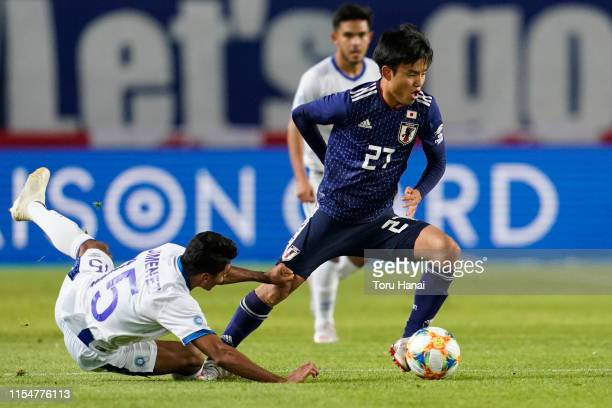 Takefusa Kubo of Japan in action against Jonathan Jimenez of El Salvador during the international friendly match between Japan and El Salvador at...