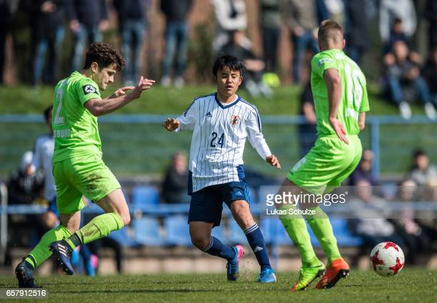 Takefusa Kubo of Japan is attacked by Mael Corboz of Duisburg and Fabio Leutenecker of Duisburg during a Friendly Match between MSV Duisburg and the...