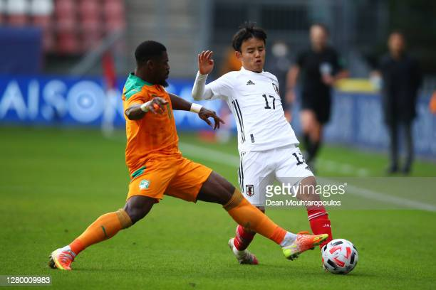 Takefusa Kubo of Japan is challenged by Serge Aurier of Ivory Coast during the international friendly match between Japan and Ivory Coast at Stadion...