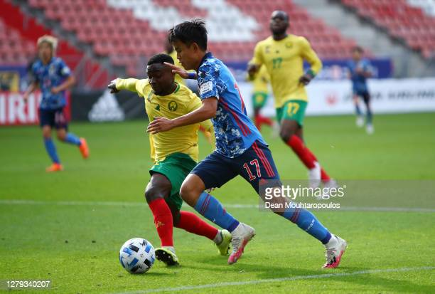 Takefusa Kubo of Japan takes on Collins Fai of Cameroon during the international friendly match between Japan and Cameroon at Stadion Galgenwaard on...