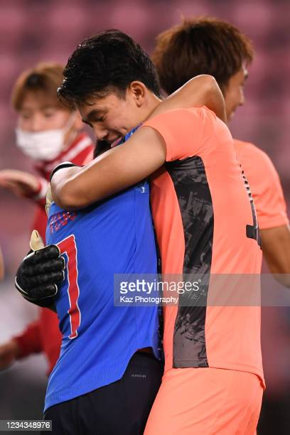 Takefusa Kubo of Japan thanks to Kosei Tani who saves the penalty kick at Penalty Shoot Out during the Men's Quarter Final match on day eight of the...