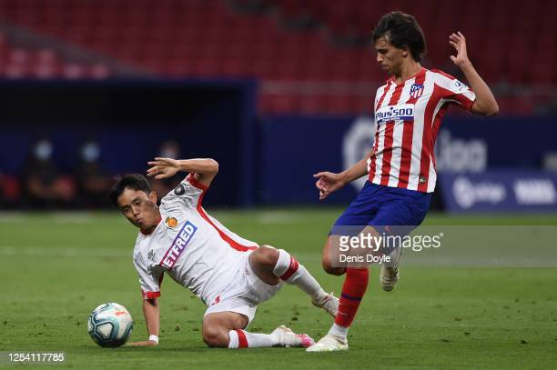 Takefusa Kubo of Mallorca falls under the challenge from Joao Felix of Atletico during the Liga match between Club Atletico de Madrid and RCD...