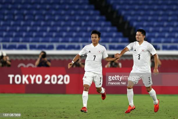 Takefusa Kubo of Team Japan celebrates with teammate Yuta Nakayama after scoring their side's first goal during the Men's Group A match between...
