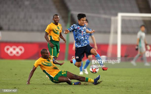 Takefusa Kubo of Team Japan is challenged by Repo Malepe of Team South Africa during the Men's First Round Group A match between Japan and South...