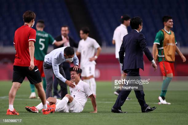 Takefusa Kubo of Team Japan looks dejected as he is consoled by Jaime Lozano, Head Coach of Mexico following defeat in the Men's Bronze Medal Match...