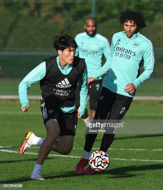 Takehiro Tomiyasu and Mohamed Elneny of Arsenal during the Arsenal 1st team training session at London Colney on October 21, 2021 in St Albans,...