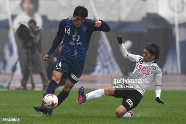 Takehiro Tomiyasu of Avispa Fukuoka is tackled by Ryota Kajikawa of Tokyo Verdy during the JLeague J1 Promotion PlayOff semi final match between...
