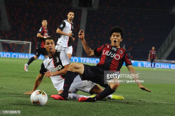 Takehiro Tomiyasu of Bologna FC battles for the ball with Juventus player Cristiano Ronaldo during the Serie A match between Bologna FC and Juventus...