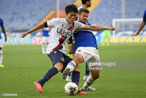 Takehiro Tomiyasu of Bologna FC tackled by Karol Linetty of UC Sampdoria during the Serie A match between UC Sampdoria and Bologna FC at Stadio Luigi...