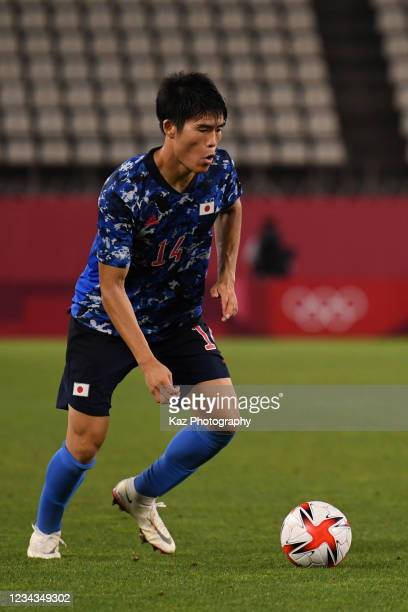 Takehiro Tomiyasu of Japan keeps the ball during the Men's Quarter Final match on day eight of the Tokyo 2020 Olympic Games at Kashima Stadium on...