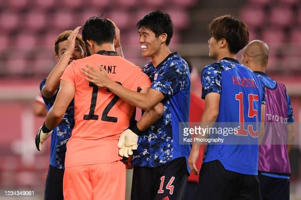 Takehiro Tomiyasu of Japan thanks to Kosei Tani who saves the penalty kick at Penalty Shoot Out during the Men's Quarter Final match on day eight of...
