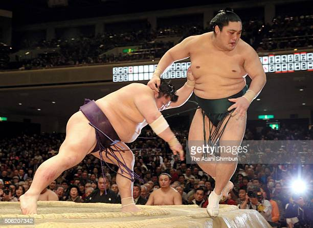 Takekaze pushes Okinoumi out of the ring to win during day twelve of the Grand Sumo New Year Tournament at Ryogoku Kokugikan on January 21 2016 in...