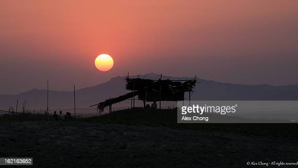 CONTENT] Taken against the beautiful glowing red sun before it disappears behind the hills the Striking silhouette of a strawandbamboo hut along the...