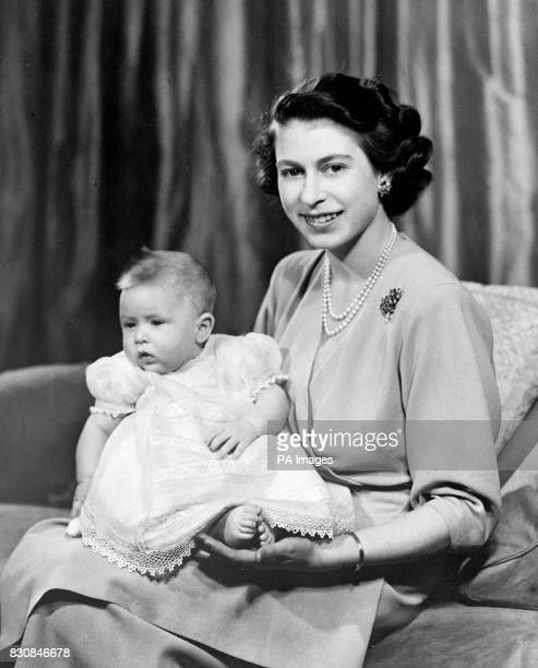 Taken by Royal command, this happy picture shows the Queen with her infant son, Prince Charles in a private room at Buckingham Palace.