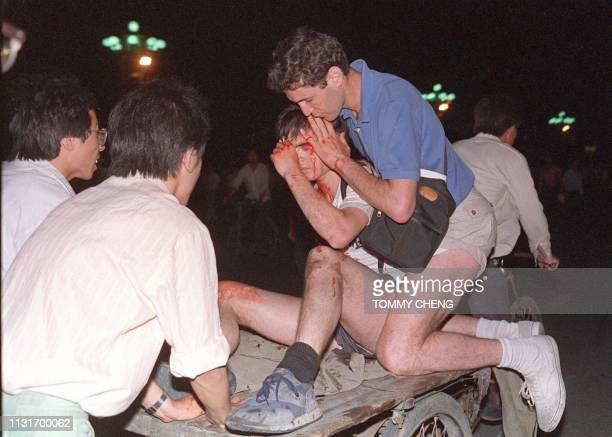 Taken care by others, an unidentified foreign journalist is carried out from the clash site between the army and students 04 June 1989 near Tiananmen...