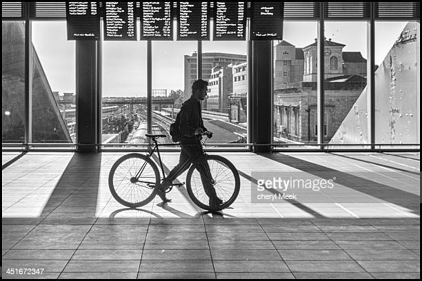 CONTENT] Taken in Reading Station morning rush hour cyclist commuter sunlight shadows departure boards concourse