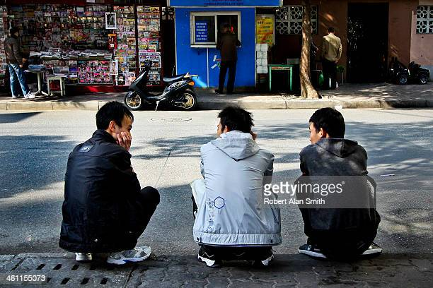 CONTENT] taken on a small street in down town Shanghai 3 men squatting at the side of the road having a discussion overlooking a small public...