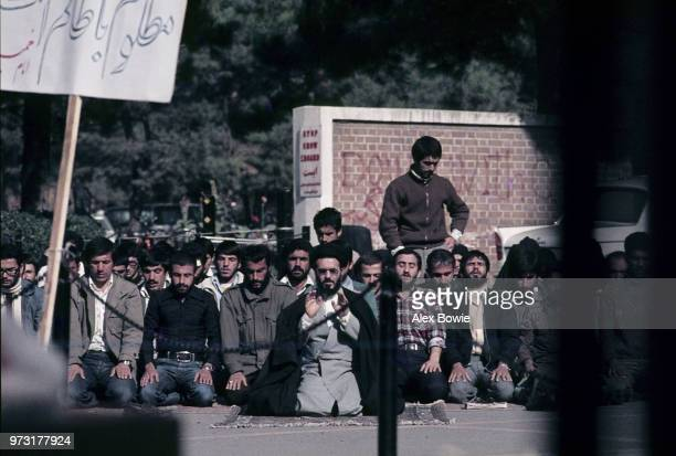 Taken through the locked gates of the US embassy in Tehran a mullah leads Iranian students in afternoon prayer a month into the Iran Hostage Crisis...
