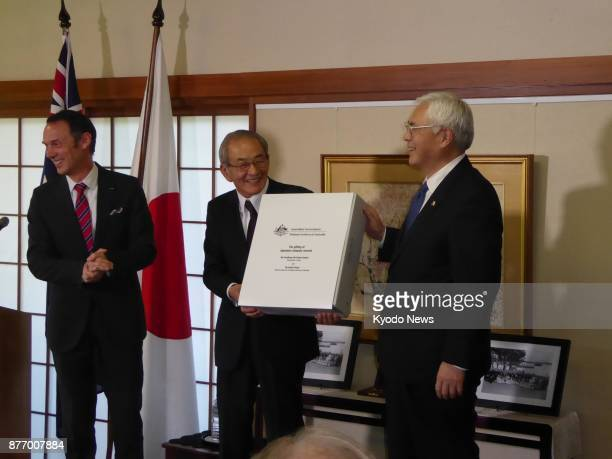 Takeo Kato president of the National Archives of Japan and Sumio Kusaka Japanese ambassador to Australia hold a document box presented by David...