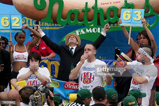 Takeru Kobayashi of Japan Joey Chestnut of San Jose and Patrick Bertoletti of Chicago stuff hotdogs in their mouths in the closing minutes of the...