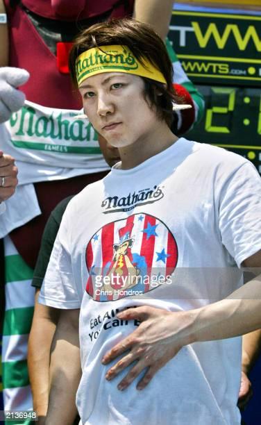 Takeru Kobayashi of Japan rubs his stomach after the annual hot dog eating contest at Coney Island July 4 2003 in New York City Kobayashi who set a...