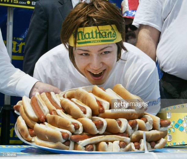 Takeru Kobayashi of Japan smiles over the pile of hot dogs that shows how much he ate at the annual hot dog eating contest at Coney Island July 4...