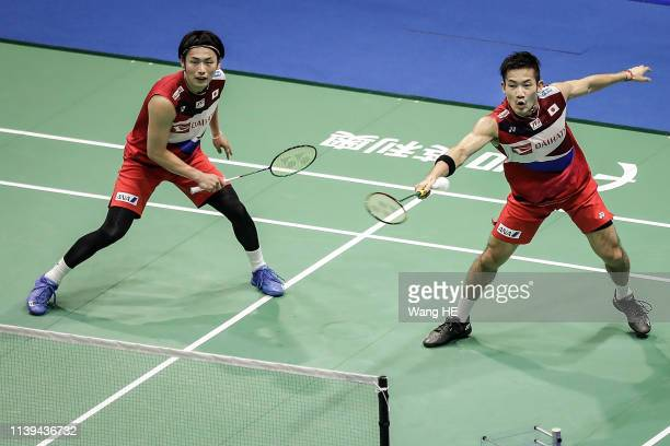 Takeshi Kamura and Keigo Sonoda of Japan hit a return during the men's doubles match against He Jiting and Tan Qiang of China at the 2019 Badminton...