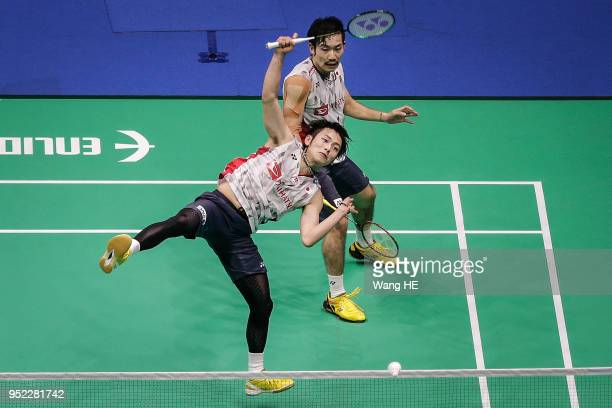 Takeshi Kamura and Keigo Sonoda of Japan hits a return during their man's doubles Semi final match against Liu Cheng and Zhang Nan of China at the...