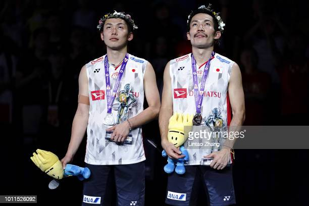 Takeshi Kamura and Keigo Sonoda of Japan react on the podium after their defeat by Li Junhui and Liu Yuchen of China in the men's doubles final on...