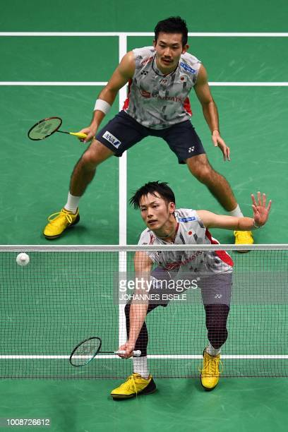 Takeshi Kamura of Japan hits a shot in front of partner Keigo Sonoda in their men's doubles match against Fajar Alfian and Muhammad Rian Ardianto of...