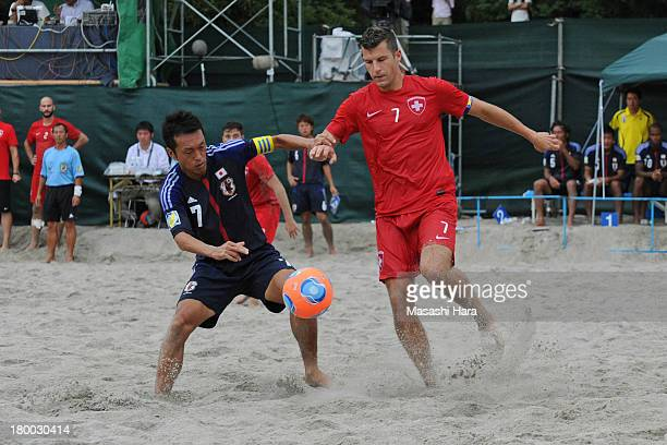Takeshi Kawaharazuka of Japan and Sandro Spaccarotella of Switzerland compete for the ball during the beach soccer international friendly between...