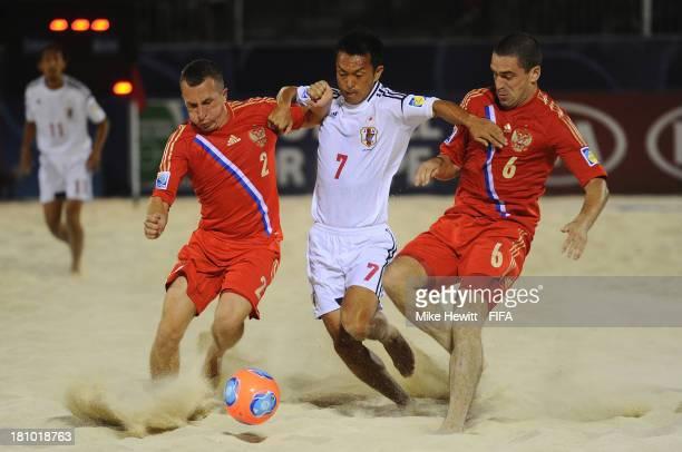 Takeshi Kawaharazuka of Japan is sandwiched between Yury Gorchinskiy and Dimitrii Shishin of Russia during the FIFA Beach Soccer World Cup Tahiti...